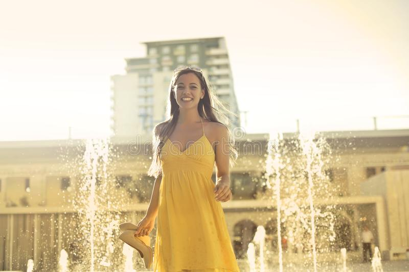 Woman Wears Yellow Spaghetti Strap Dress Stands Near Water Fountain royalty free stock image