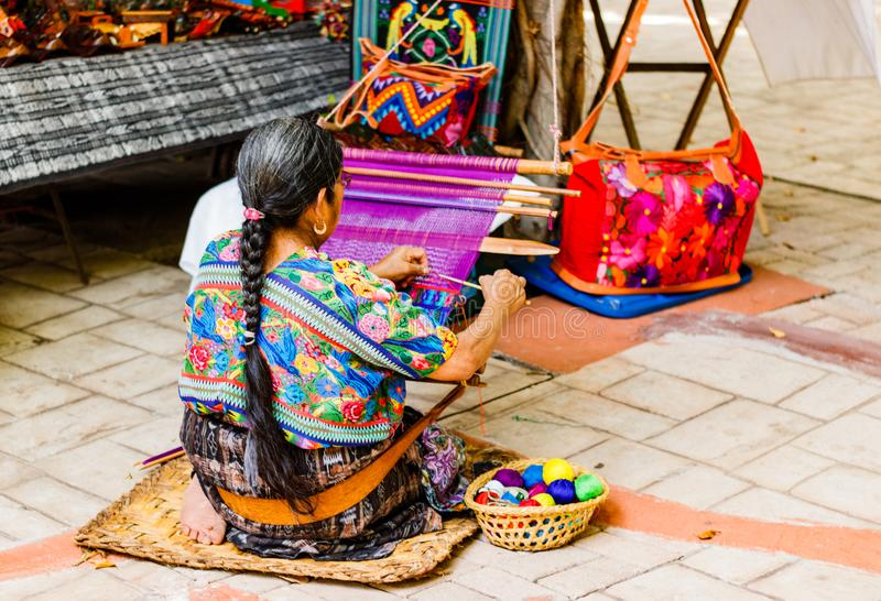 Woman weaving in an old village in Guatemala. royalty free stock photo
