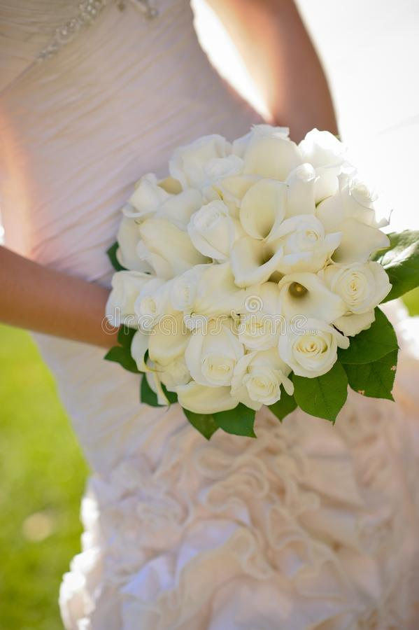 Woman in Wedding Dress Holding White Flower Bouquet stock photos