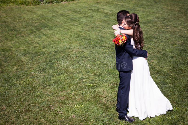 Woman in wedding dress next to her husband on grass royalty free stock image
