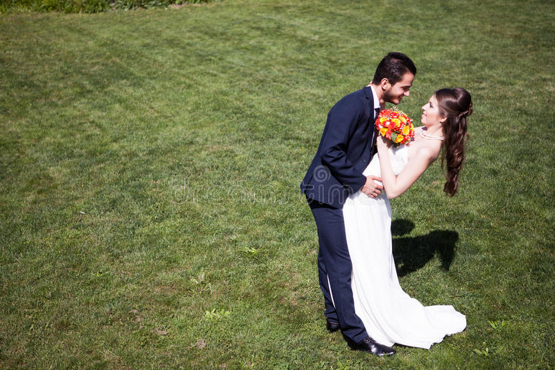 Woman in wedding dress next to her husband on grass stock photos