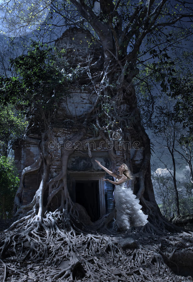The woman in a wedding dress worships to the Moon at an entrance to the thrown temple, night, Cambodia royalty free stock images
