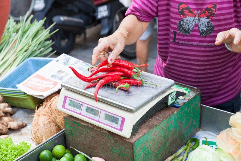 Woman is weighing chili peppers on the scales stock photos