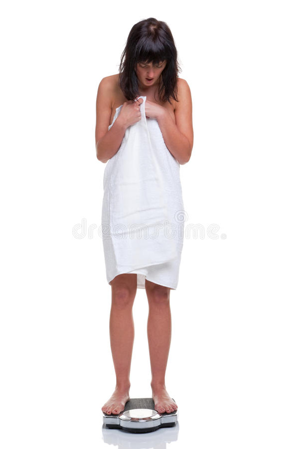Woman weighing herself. A woman wrapped in a towel weighing herself on bathroom scales,she has a shocked expression, isolated on a white background stock photo
