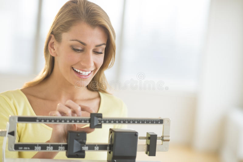 Woman Weighing Herself On Balance Scale. Happy young woman weighing herself on balance scale at health club stock image