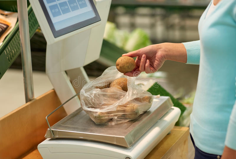 Woman weighing potatoes on scale at grocery store. Shopping, sale, consumerism and people concept - woman weighing potatoes on scale at grocery store stock photography