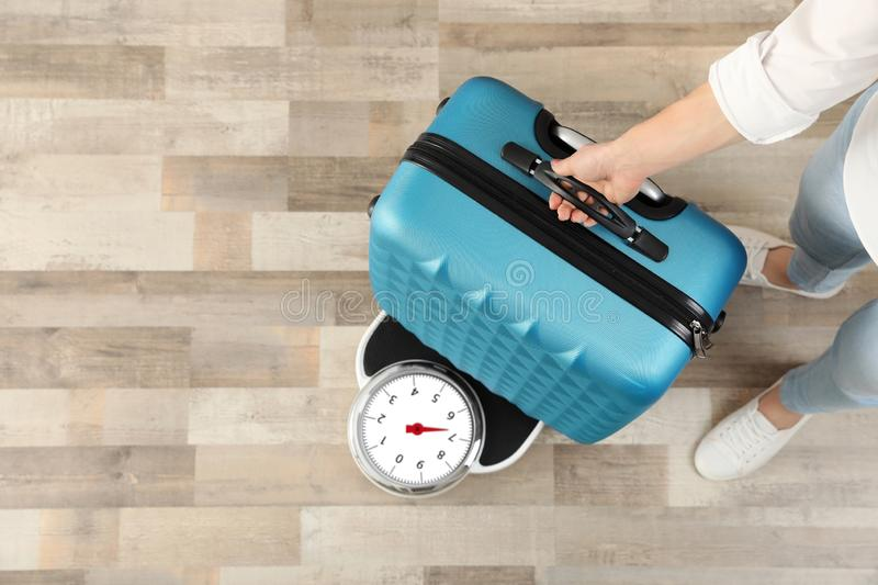 Woman weighing suitcase indoors, top view. Space for text royalty free stock photos