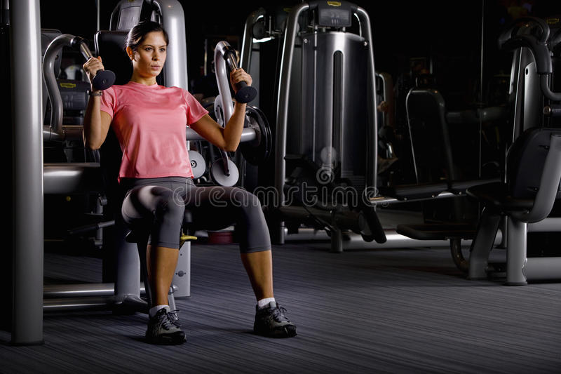 Woman weight lifting with exercise equipment in health club royalty free stock images
