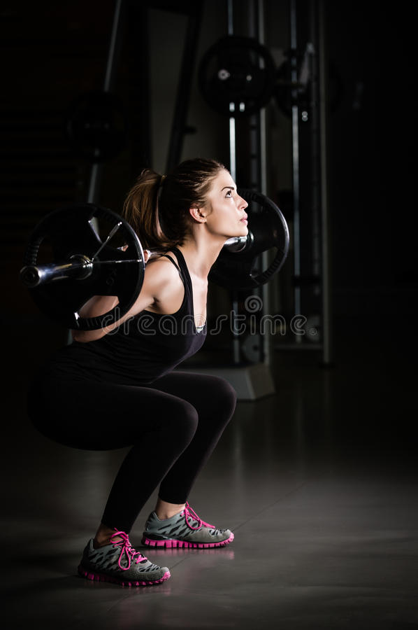 Woman weight training at gym.Devoted body builder girl lifting weights in gym and doing squats low key photo royalty free stock image