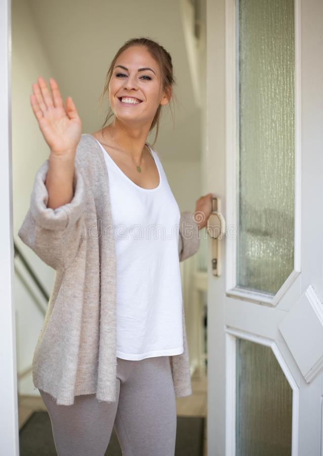 Woman welcome friends at open front door. Cheerful young woman welcome friends at open front door and welcome royalty free stock image