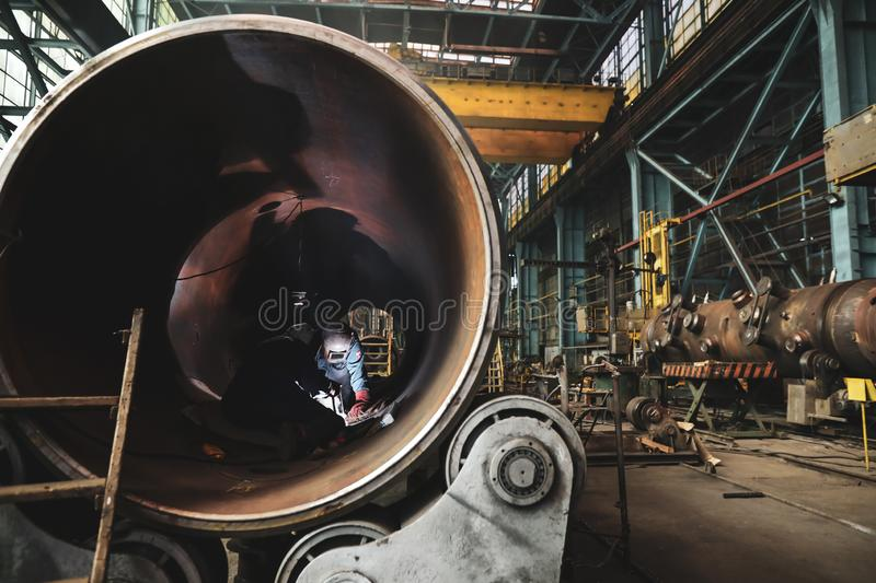 Woman welder in a dirty and old but still functioning metal works, old fashioned, factory.  royalty free stock photography