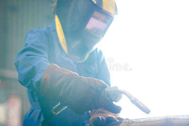 Woman Welding Metal. Waist up portrait of female worker welding metal at factory wearing full protective gear and mask, copy space stock photo