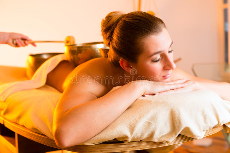 Woman at Wellness massage with singing bowls. Woman in wellness and spa setting having a singing bowl massage therapy stock photo