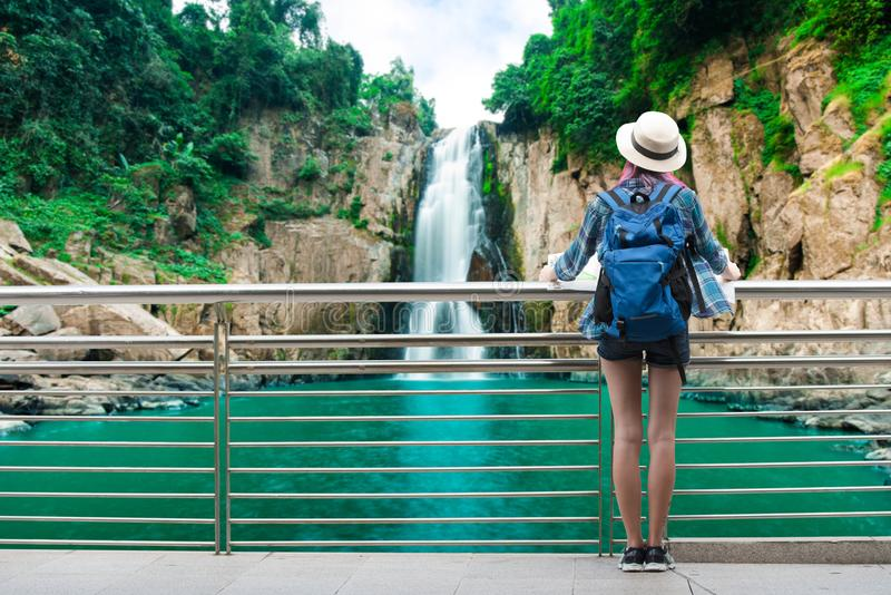 Woman westerner travel in backpack with map looking at Hew Naro. K Waterfall in Khaiyai national park in Thailand royalty free stock image