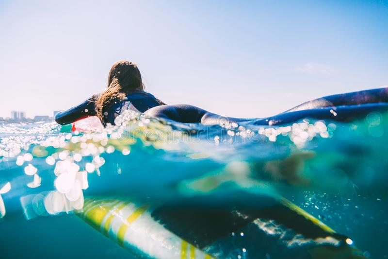 Surfer woman in wetsuit on the surfboard. Woman with surfboard in ocean during surfing stock photo