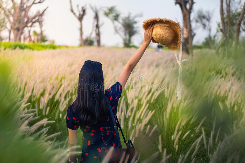 Woman at wheat field at sunset. Woman having fun at a wheat field at sunset, girl, dress, hat, rural, yellow, view, shape, sky, day, happy, person, silk, travel royalty free stock image
