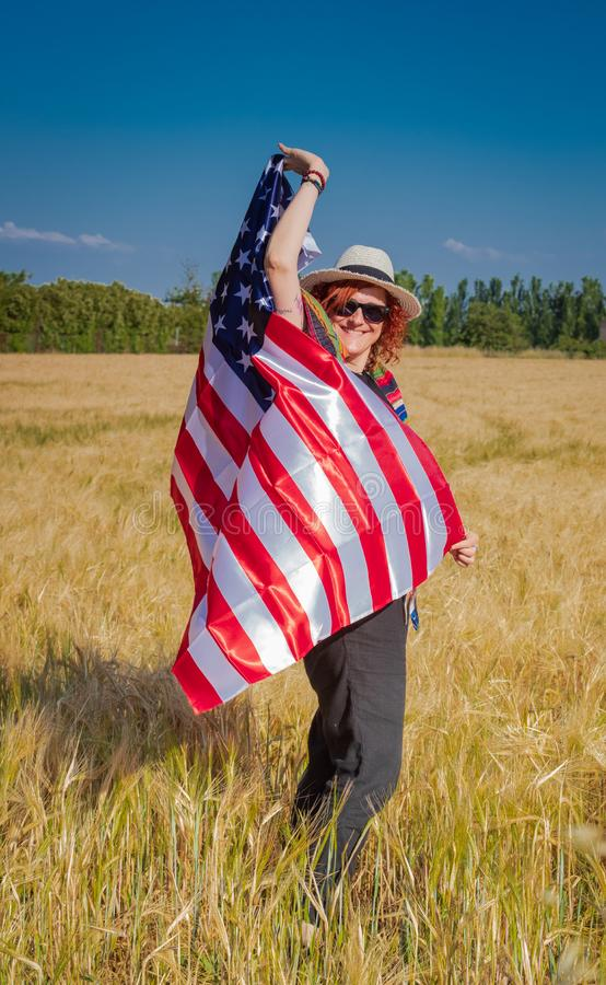 Woman in a wheat field with a USA flag royalty free stock image