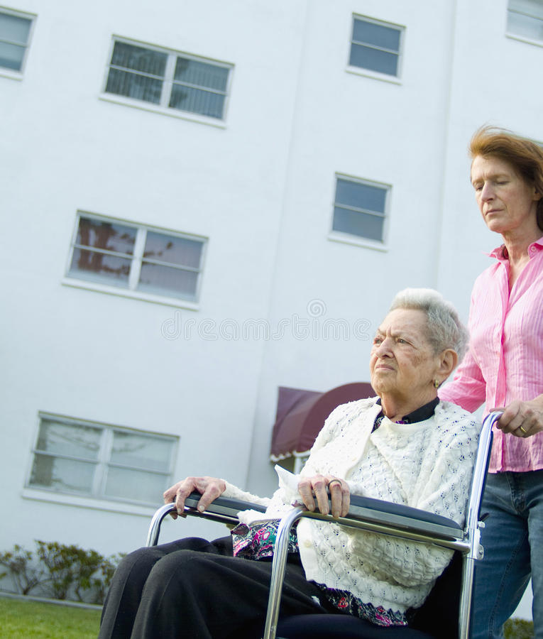 Woman in wheelchair with caregiver. Elderly woman in wheelchair outdoors with caregiver royalty free stock photography