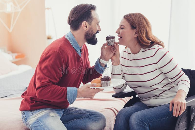Woman in a wheelchair eating cakes with her husband and looking happy. Eating sweets. Cheerful young women in a wheelchair closing her eyes while eating royalty free stock image