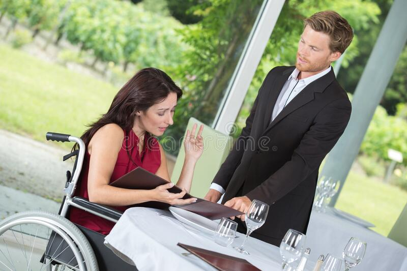 Woman in wheelchair eating at restaurant stock photo