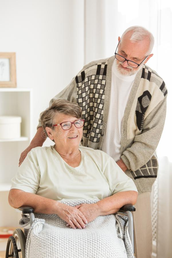 Senior woman on wheelchair with elderly friend behind her. Woman on wheelchair with elderly friend behind her stock images