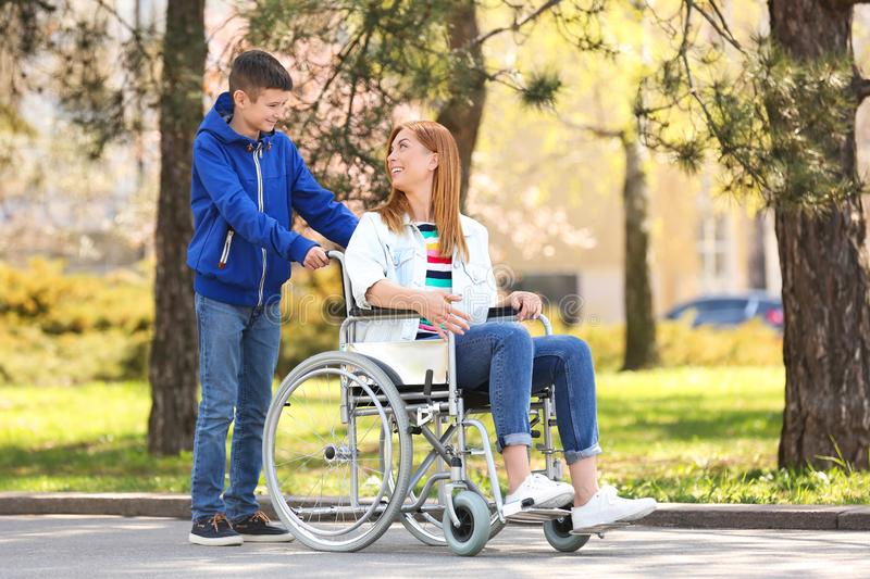 Woman in wheelchair and her son at park royalty free stock image