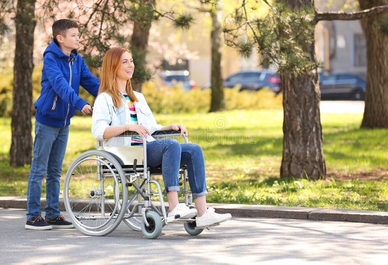 Woman in wheelchair and her son at park royalty free stock photos