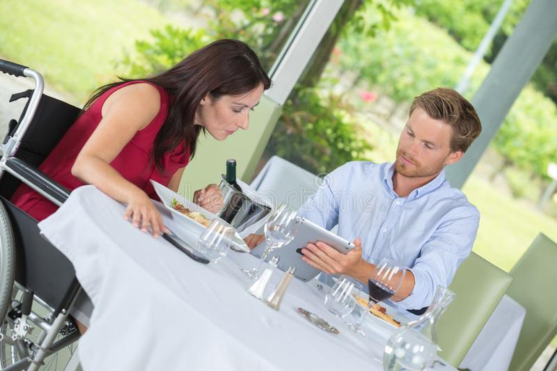 Woman in wheelchair with husband in restaurant stock image