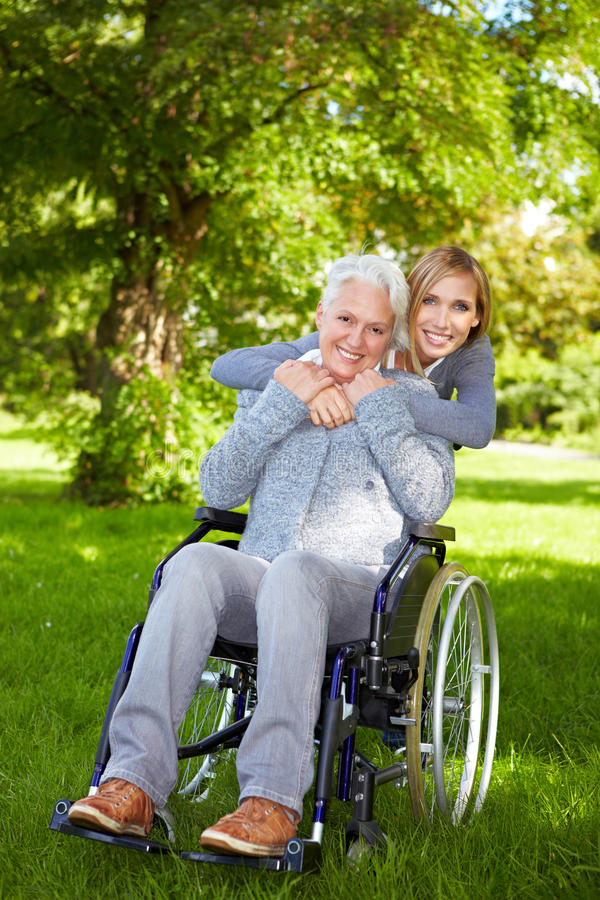 Woman in wheelchair in nature. Happy woman in wheelchair with young woman in nature stock image