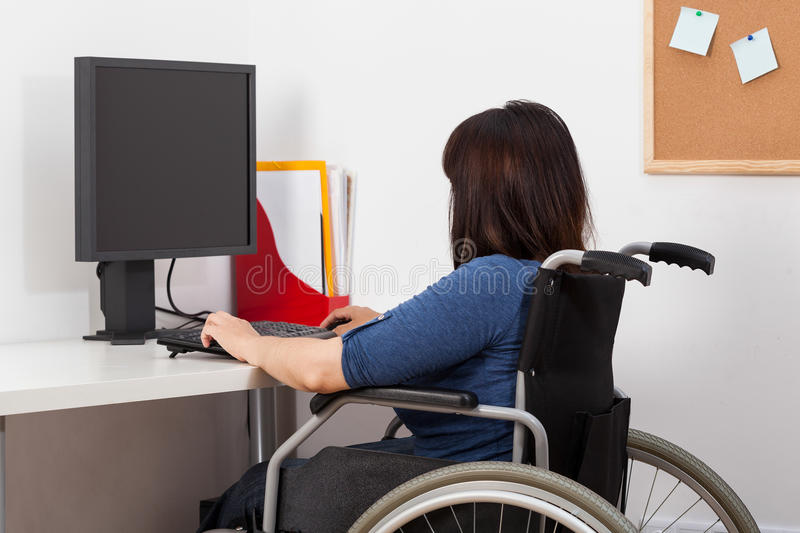 Woman on wheelchair working in office royalty free stock images