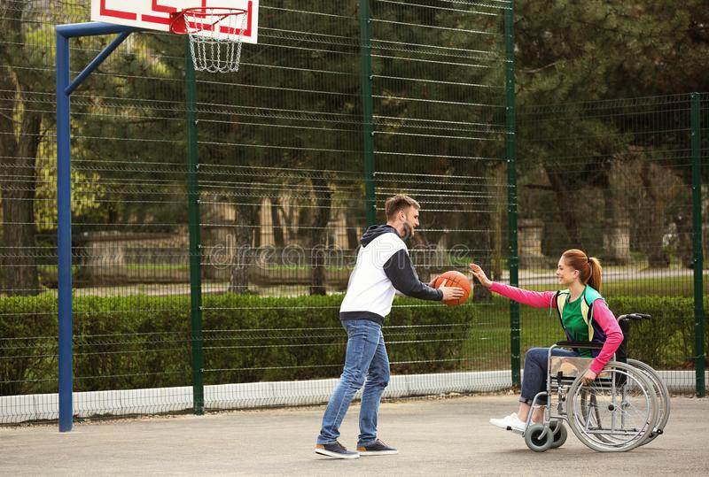 Woman in wheelchair and young man playing basketball on ground royalty free stock photo