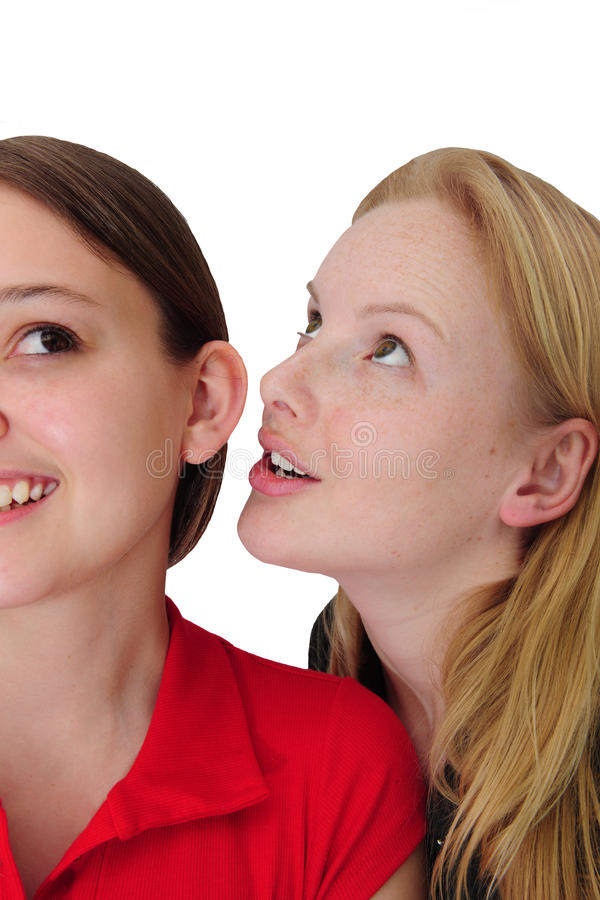 Woman whispering in friend´s ear royalty free stock photography