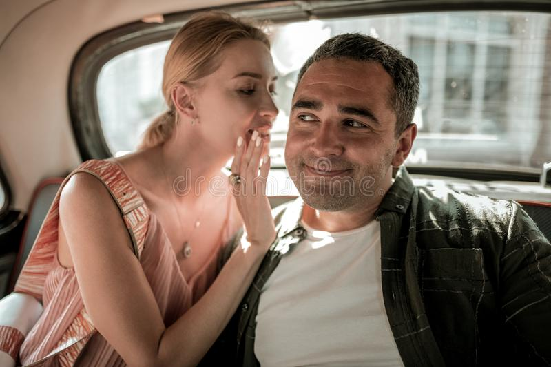 Woman whispering her husband about the car driver. royalty free stock photo