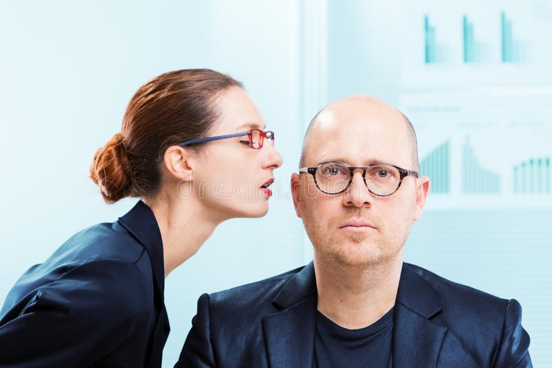 Woman whispering into man ear at office stock photo
