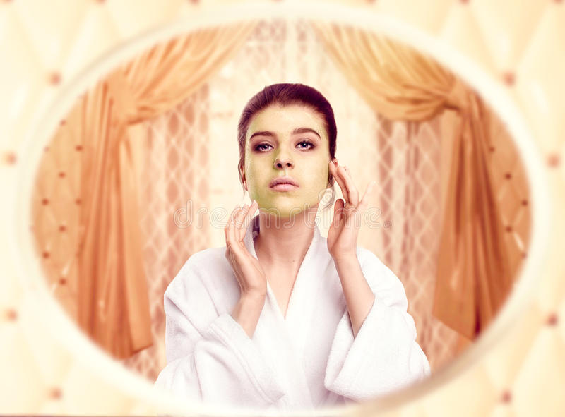 Woman in white bathrobe gets cream mask for face royalty free stock photo