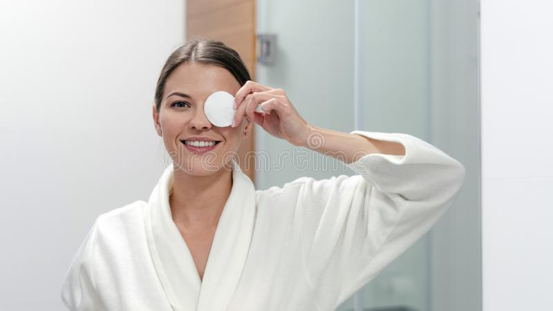 Woman in white bathrobe holding cotton pad in hands stock images