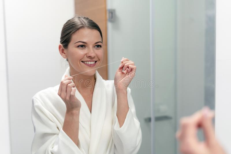 Woman in white bathrobe holding dental floss in hands royalty free stock image