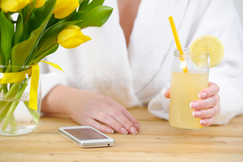 Woman in a white Bathrobe. On the table yellow tulips, smartphone and lemonade in the hand. Woman in a white Bathrobe. On the table yellow tulips, smartphone royalty free stock images