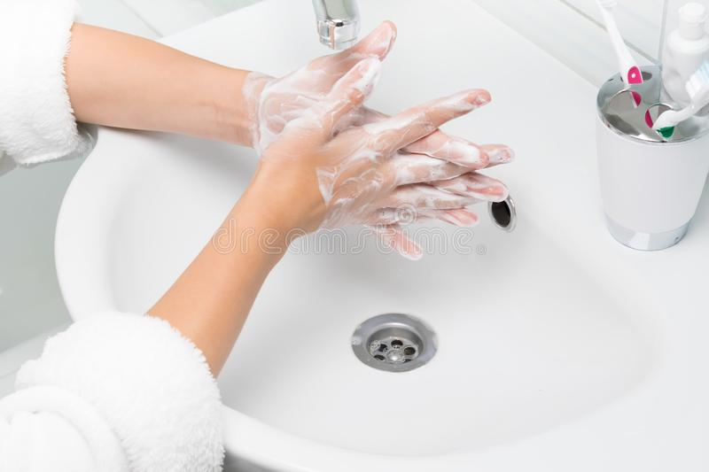 Woman in white bathrobe washes her hands with soap in the bathroom, close-up royalty free stock photo