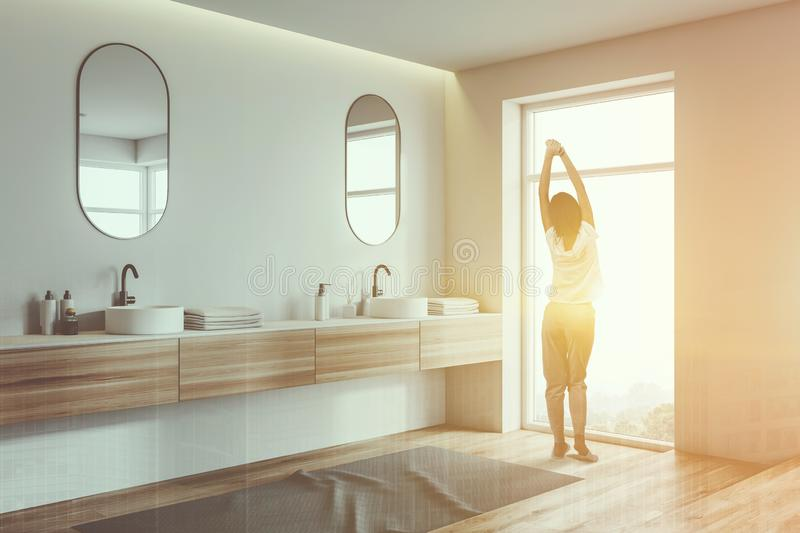 Woman in white bathroom corner with double sink stock photo
