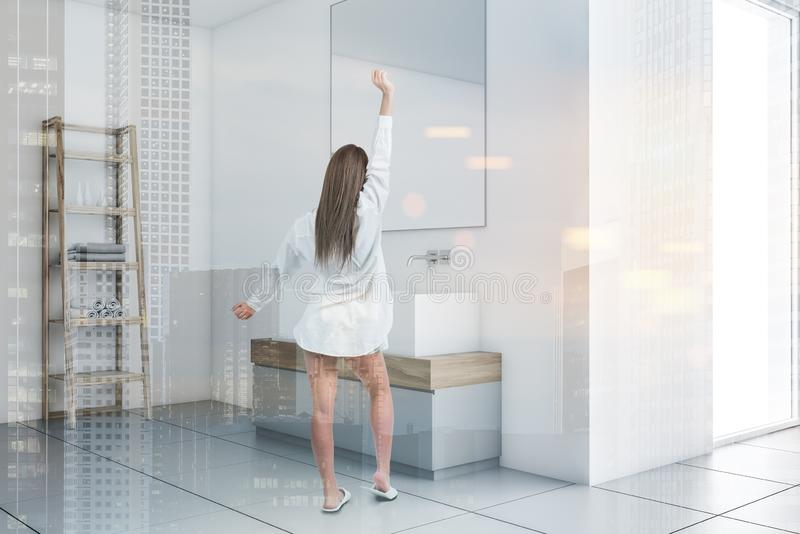 Woman in white bathroom corner with double sink royalty free stock image