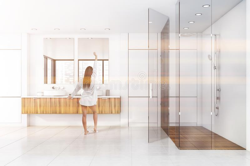 Woman in white bathroom with shower and sink. Young woman standing in sunlit bathroom with white walls, tiled floor, double sink on wooden countertop and shower royalty free stock images