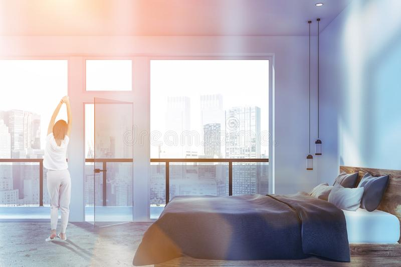 Woman in white bedroom with balcony royalty free stock photo