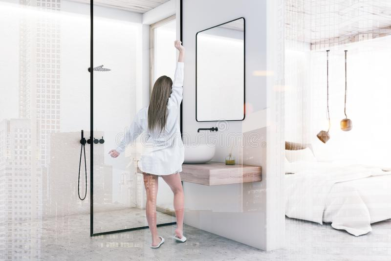 Woman in white bedroom and bathroom with shower. Woman in pajamas standing in modern bathroom interior with white walls, concrete floor, sink with mirror and stock photography
