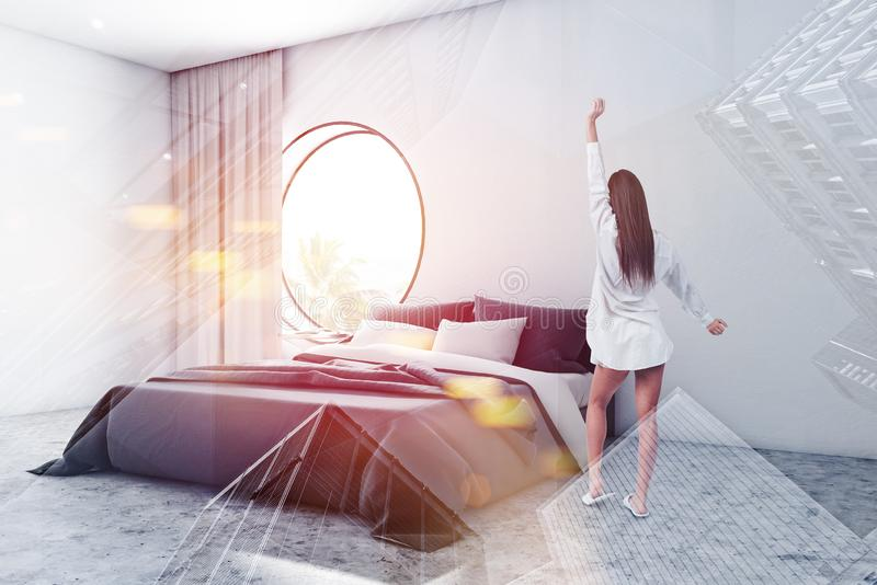 Woman in white bedroom corner with round window. Rear view of young woman standing in modern bedroom with white walls, concrete floor, king size bed and round royalty free stock photography