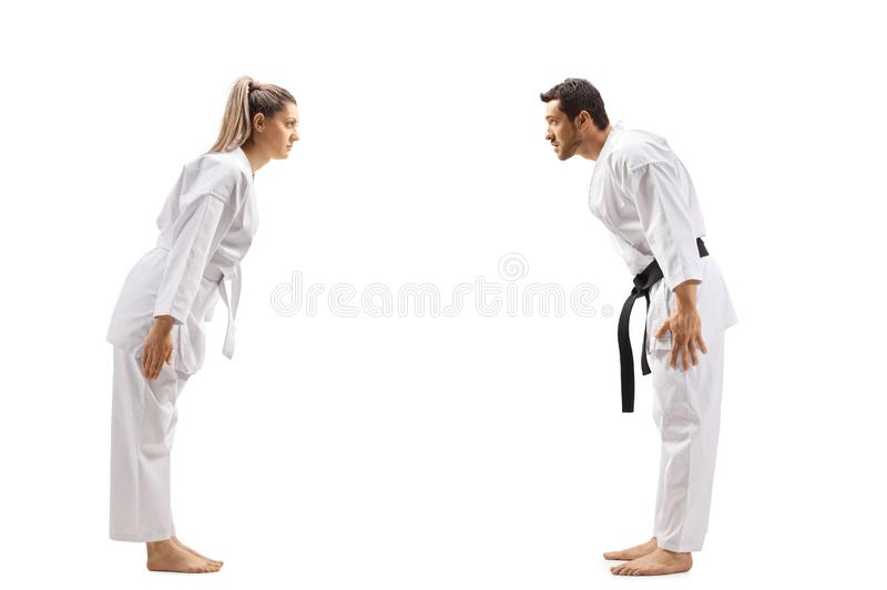 Woman with white belt in karate and a man with black belt bowing at each other. Full length profile shot of a women with white belt in karate and a men with stock images