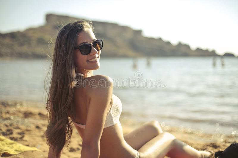 Woman in White Bikini Set Sitting Near Seashore royalty free stock photos