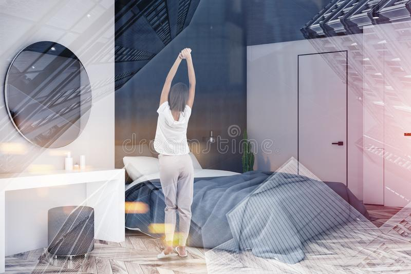Woman in white and black bedroom with mirror. Rear view of woman in pajamas standing in white and black bedroom interior with wooden floor, master bed and makeup stock images