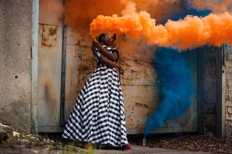 Woman in White and Black Dress Holding Orange Smoke stock photo