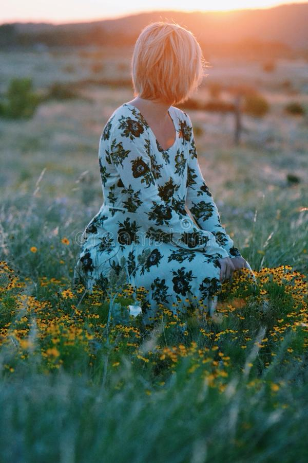 Woman In White And Black Floral Themed Dress Sitting On Green Grass Field Free Public Domain Cc0 Image